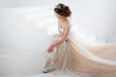 Bride sits on the stairs. Portrait of a beautiful girl in a wedding dress. Dancing Bride, white background. Stock Photo