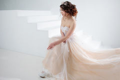 Bride sits on the stairs. Portrait of a beautiful girl in a wedding dress. Dancing Bride, white background. Stock Images