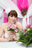 Bride sits at table with candles Stock Photography