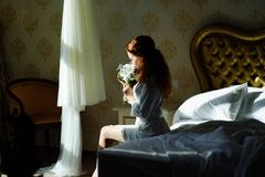 Beautiful sexy redhair lady in elegant white panties and peignoir. Fashion portrait of model indoors. Beauty woman with lace linge. The bride sits at the window Royalty Free Stock Image
