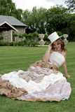 Bride Sitting. A bride sitting on grass holding a hat Stock Photos