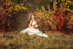 Bride sitting in autumn bush. Beautiful bride in a wedding dress sitting near the bushes in the autumn forest and holds a wedding bouquet Stock Image