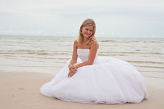Bride sitting on a beach Royalty Free Stock Photos