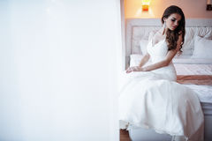 Bride sitting on the bed Stock Photography