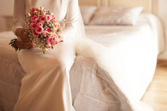 Bride sitting in the bed holding the bouquet in the white colore Stock Photo