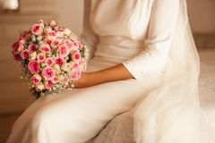 Bride sitting in the bed holding the bouquet in the white colore Royalty Free Stock Images