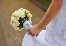 Bride sitting on bench holding wedding bouquet of various flower Royalty Free Stock Image