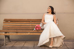 Bride sitting on a bench outdoors Stock Image