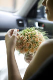 Bride sitting in car. Smiling bride sitting in car hold bouquet of rose royalty free stock photo