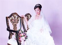 Bride sitting on chair with flowers Royalty Free Stock Photography