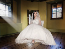 Bride sitting on a chair in a room Royalty Free Stock Photos