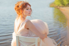 Bride sitting on a chair in the water realized dress and watch the sunset Stock Photos