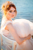 Bride sitting on a chair in the water realized dress and watch the sunset Royalty Free Stock Photo