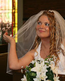 Bride sitting in a church pew holding her veil stock photo