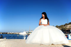 Bride sitting down in a port in Santorini, GREECE. A shot with a brunette bride on a small port in Santorini Stock Images