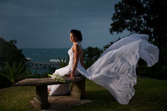 Bride sitting with dress blowing in the wind Stock Image