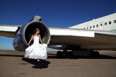 Bride sitting in engine of retired commercial airplane Royalty Free Stock Image