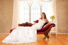 Bride sitting on fainting couch by window Royalty Free Stock Photography