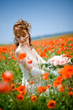 Bride sitting in field of flowers royalty free stock photography