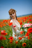 Bride sitting in field of flowers Stock Image