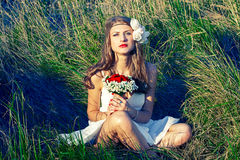 Bride sitting with flowers on the grass in park. Beautiful girl with a bouquet of flowers sitting in the grass Royalty Free Stock Image