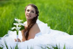 Bride sitting on the grass Royalty Free Stock Photo