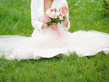 Bride Sitting on Grass Stock Photo