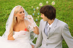 Bride sitting with groom and blowing bubbles Royalty Free Stock Image