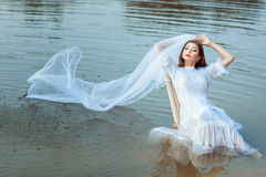 Bride sitting in a lake, her veil wet. Stock Image