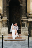 Bride sitting on lap of the bride. Bride sitting on the lap of the bride against the background of an old building Royalty Free Stock Image
