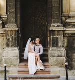 Bride sitting on lap of the groom. Bride sitting on the lap of the groom against the background of an old building Royalty Free Stock Images