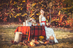 Bride sitting near the table in autumn forest. Beautiful bride sitting near the table surrounded by vegetables, fruits and flowers in the autumn forest Stock Image