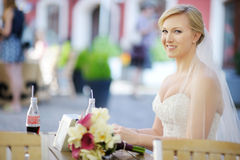 Bride sitting at an outdoor cafe Stock Image