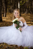 Bride sitting in a park Stock Image