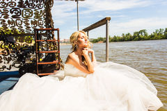 Bride sitting on the pier royalty free stock photography