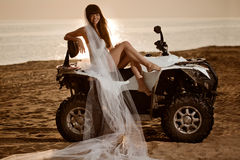Bride sitting on a quad bike on the beach Stock Image