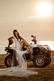 Bride sitting on a quad bike on the beach Royalty Free Stock Photography