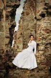 Bride sitting on ruins Royalty Free Stock Image