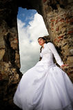 Bride sitting on ruins Stock Photo
