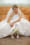 Bride sitting on sofa waiting for ceremony Royalty Free Stock Image