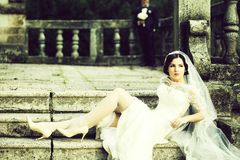 Bride sitting on stairs stock photography