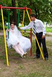 Bride sitting on swings and groom standing near Royalty Free Stock Photo