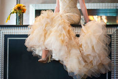 Bride sitting on the table and keeps trail. Only the lower part stock photography