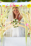 Bride Sitting Under Decorated Canopy At Wedding Stock Images