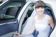 Bride sitting in wedding car Stock Photos