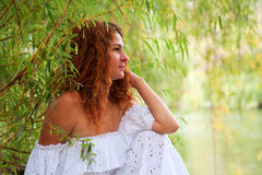 Bride sitting at willow by the rive. Beautiful young red-haired woman in white dress with flower in her hair or bride sitting at willow by the river, resting and stock images