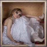 Bride sitting in a wooden box Royalty Free Stock Photo