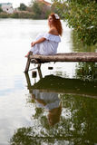 Bride sitting on wooden bridge Royalty Free Stock Photos