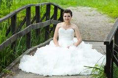 Bride sitting on wooden bridge Stock Photos
