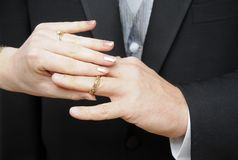 Bride slipping ring on finger Royalty Free Stock Photography